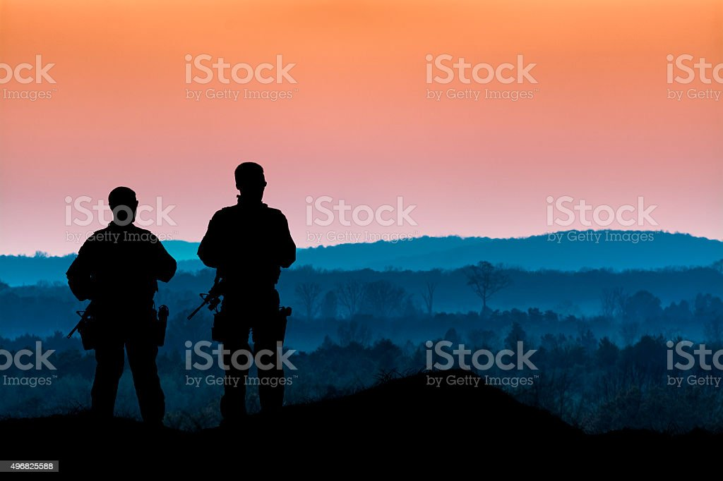 Men with Guns Overlook a Forest at Dusk stock photo