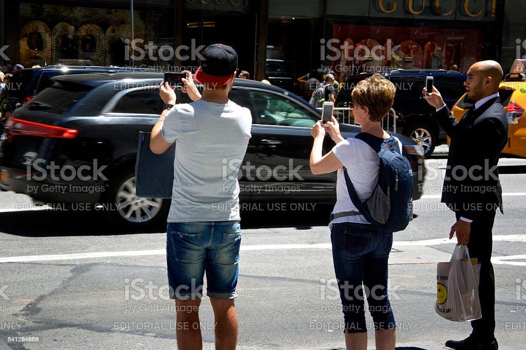 Men & woman taking smartphone photos, Midtown Manhattan, NYC stock photo