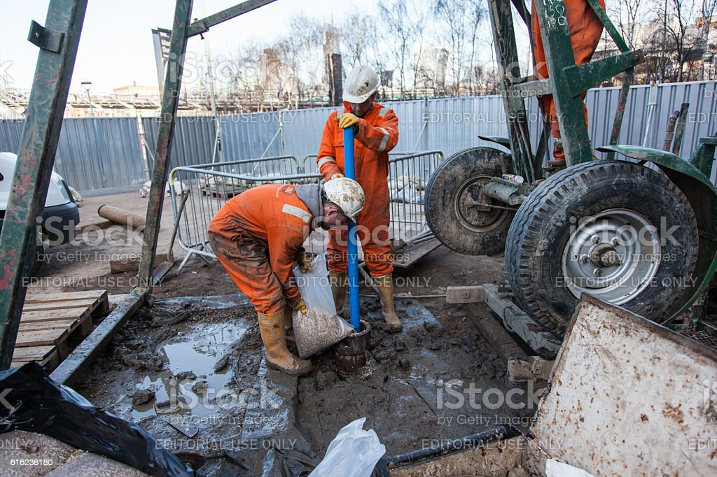 men work on borehole to fill the hole with gravel stock photo