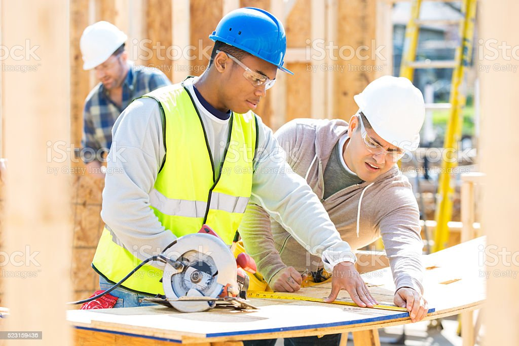 Men work together at construction site stock photo