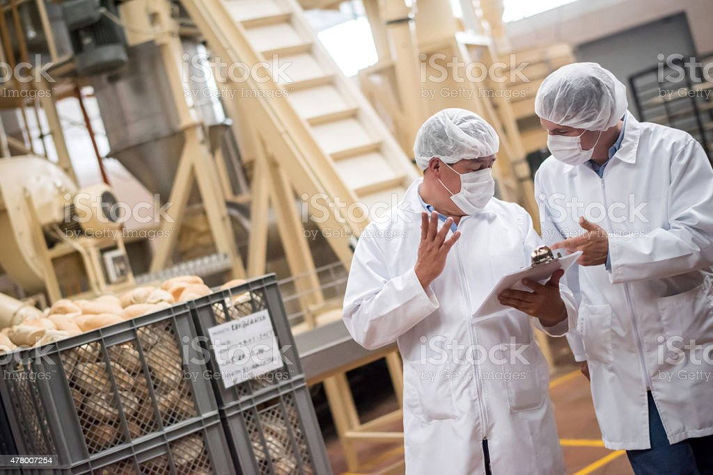 Men  working at a bread factory stock photo