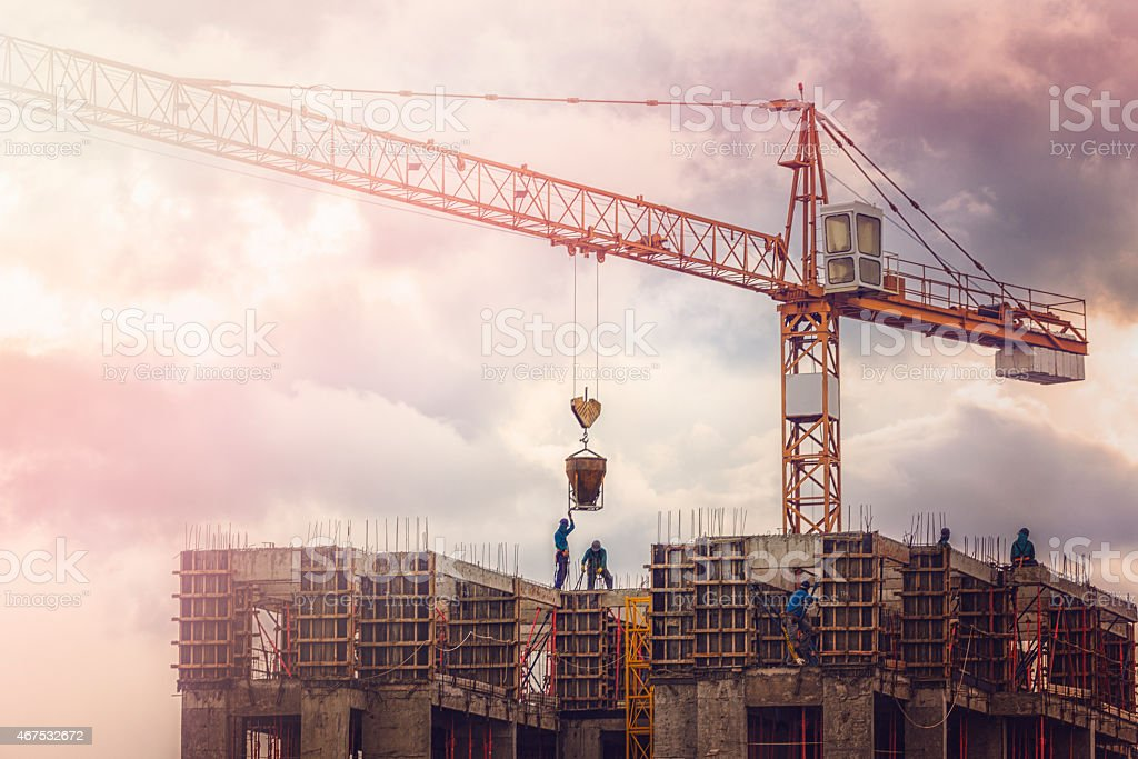 Men working on high while the sun sets. stock photo