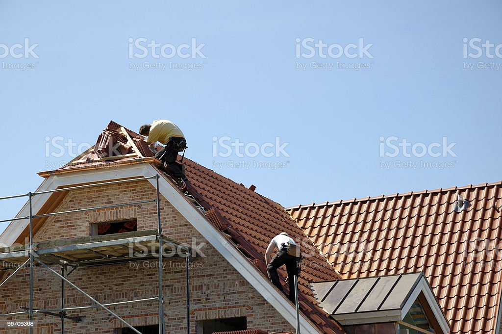 2 men working on red roof of a house with scaffolding  stock photo