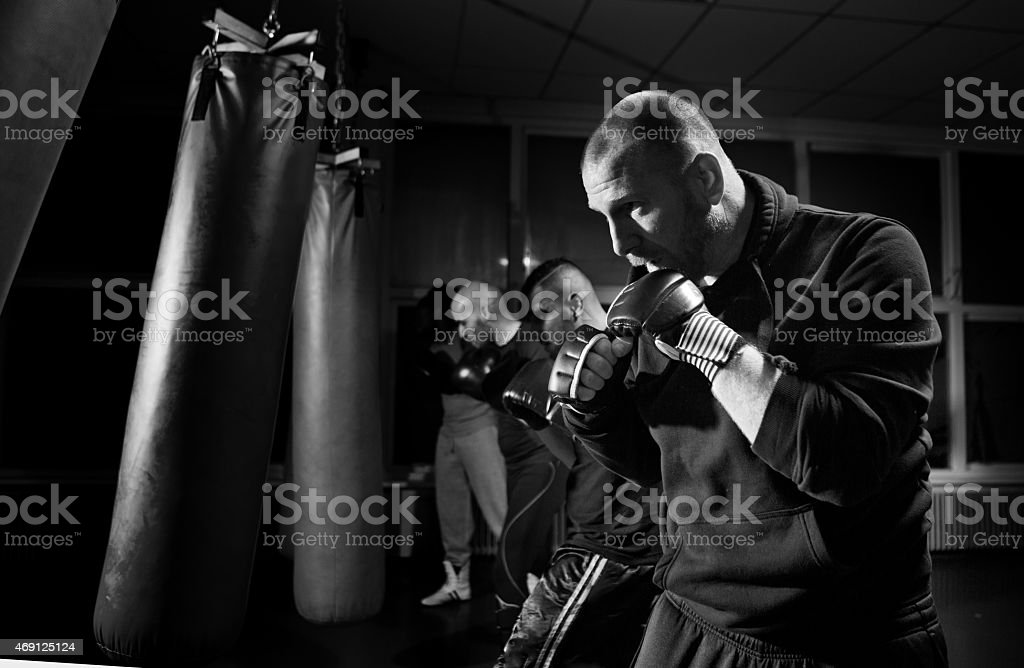 men working out with punch bag stock photo