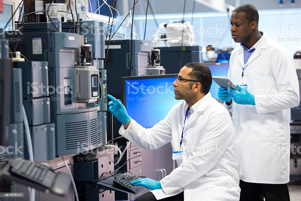Men Working With Specialist Scientific Equipment for Measuring Chemicals. stock photo
