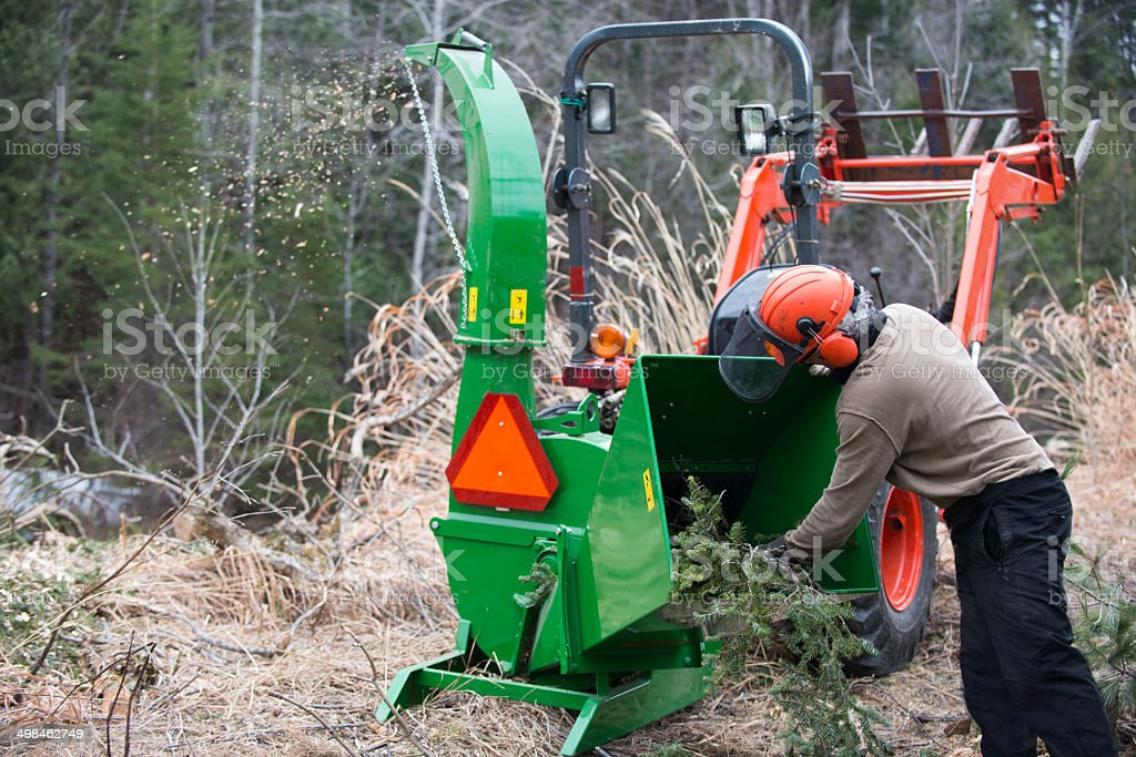 Men working with wood chipper and tractor stock photo