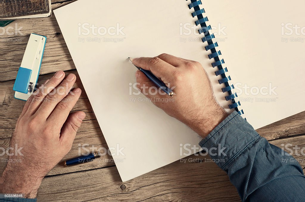 Men writes in an open notebook with blank pages stock photo