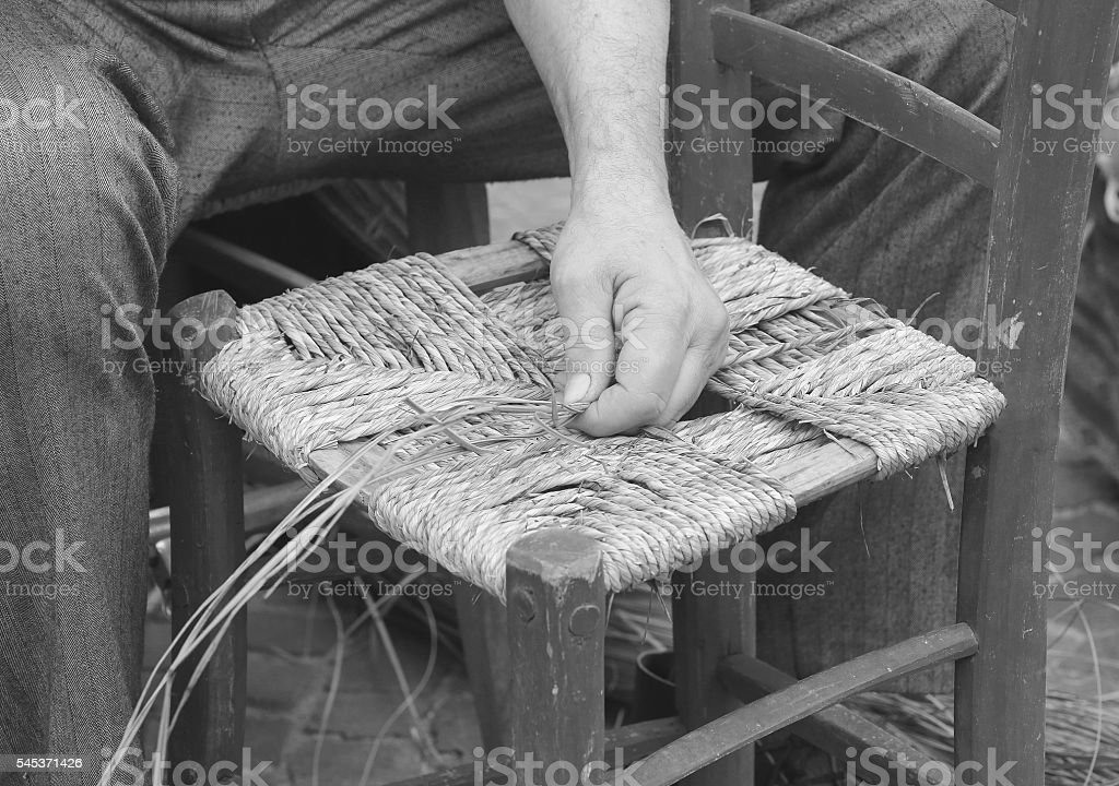 mender of chairs while repairing an old wooden chair stock photo