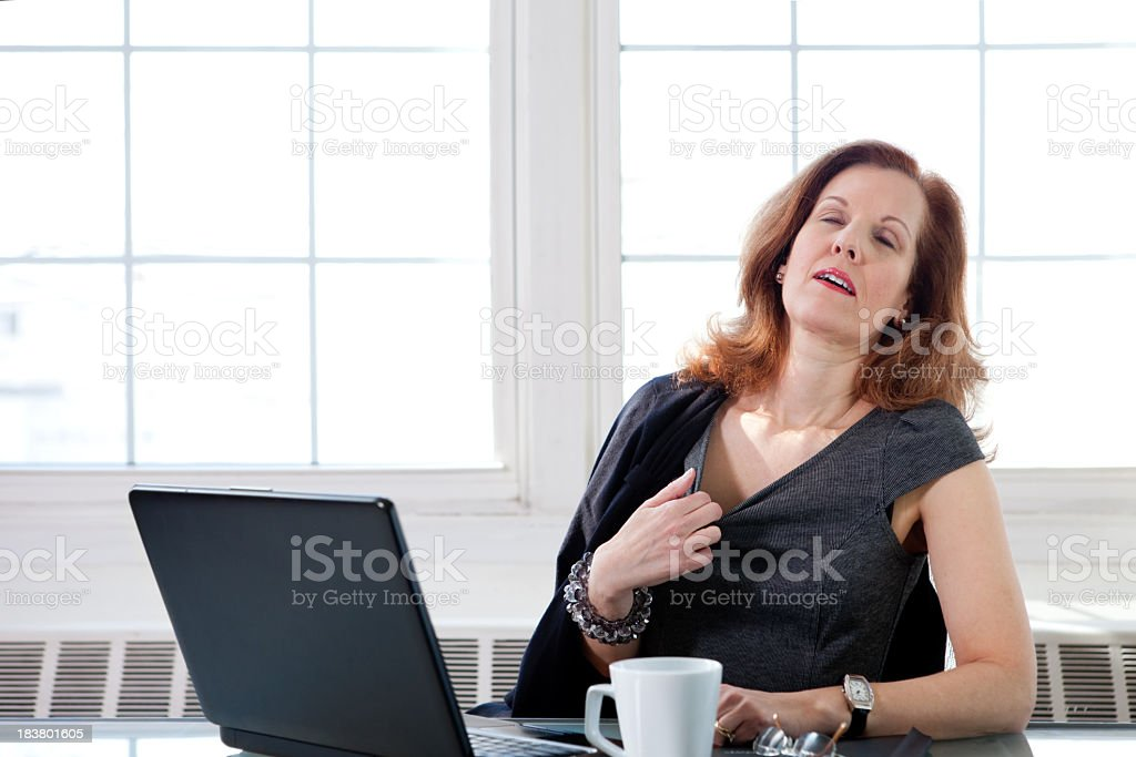 Menopausal woman having a hot flash at the office stock photo