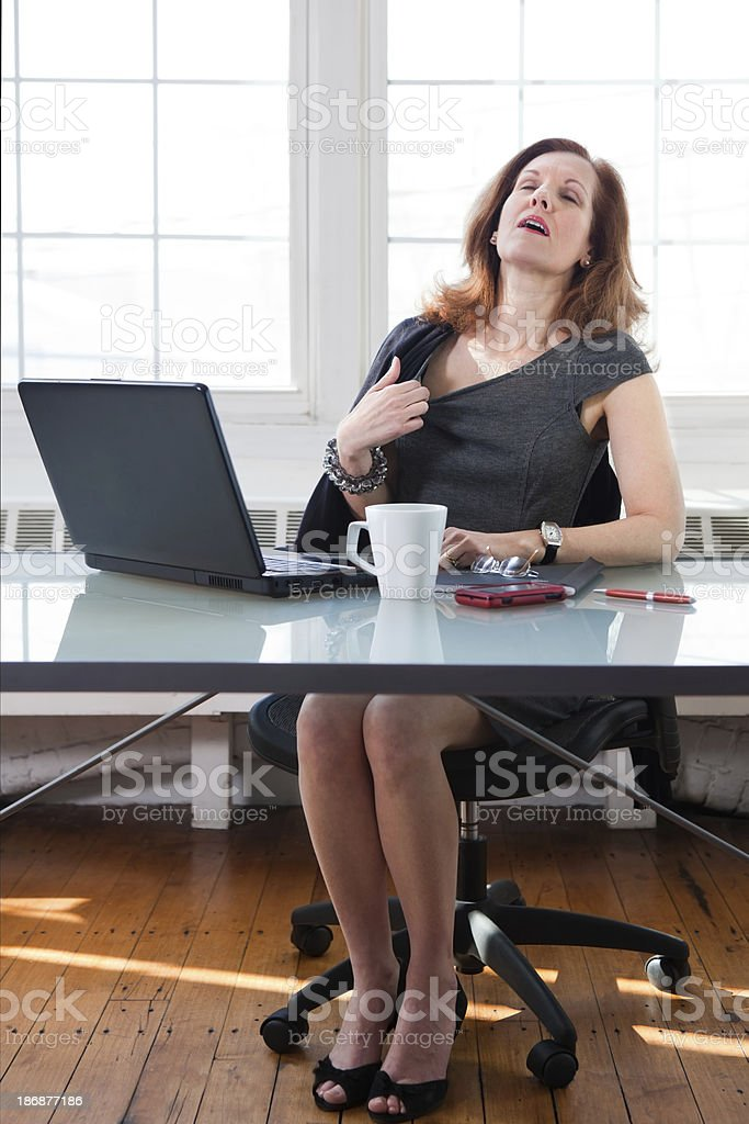 Menopausal woman having a hot flash at the office royalty-free stock photo