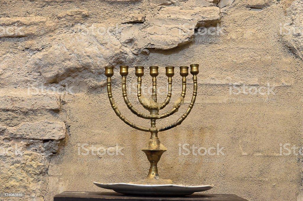 Menorah against the ancient stone wall stock photo