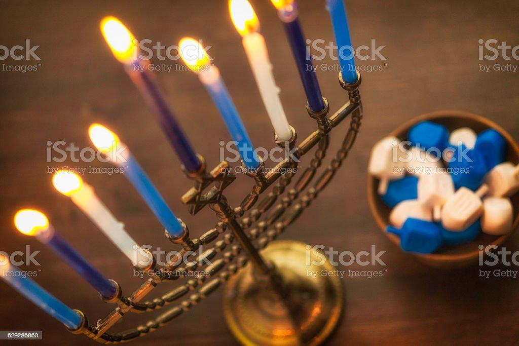 Menorah with burning candles and dreidel. Hanukkah preparations stock photo