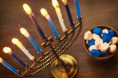 Menorah with burning candles and dreidel. Hanukkah preparations