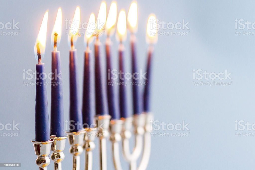 Menorah with burning candles for Hanukkah on blue background stock photo