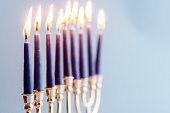Menorah with burning candles for Hanukkah on blue background