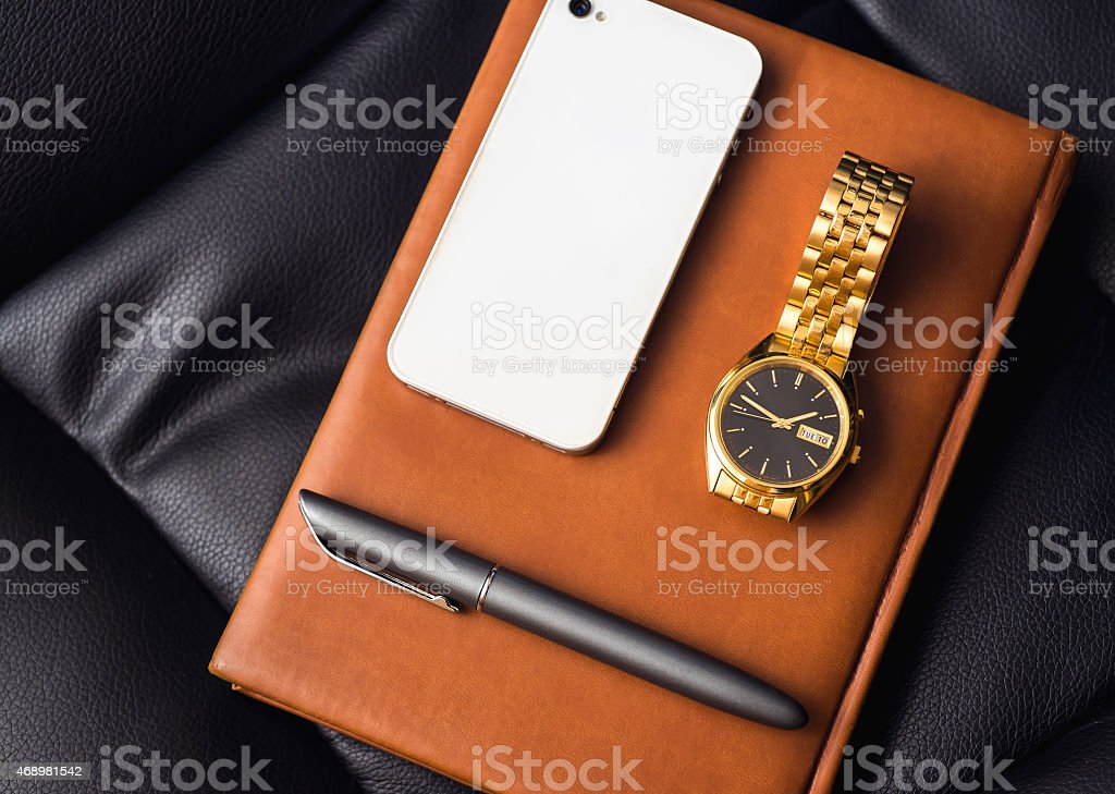 Men's accessory, golden watch, pen and mobile phone on stock photo