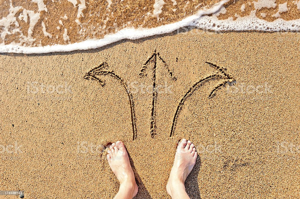 men's bare feet in the sand and arrows stock photo
