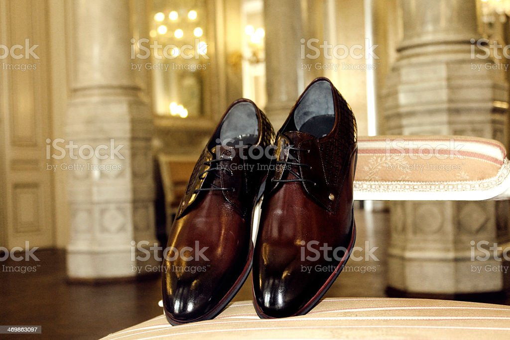 Men's brown dress shoes on the arm of an elegant chair stock photo