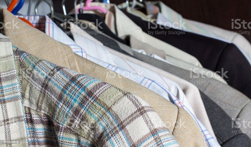 Men's clothes hanging on rack in a row in closet stock photo