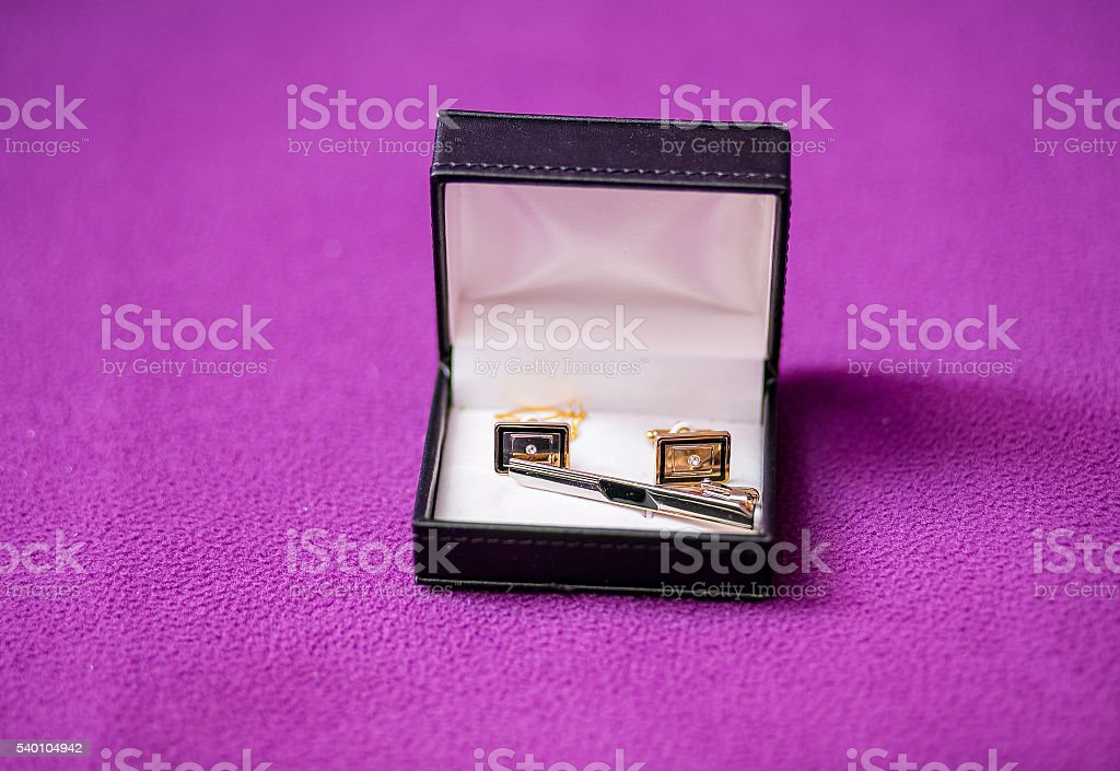 Men's cufflinks in the box on purple fabric stock photo