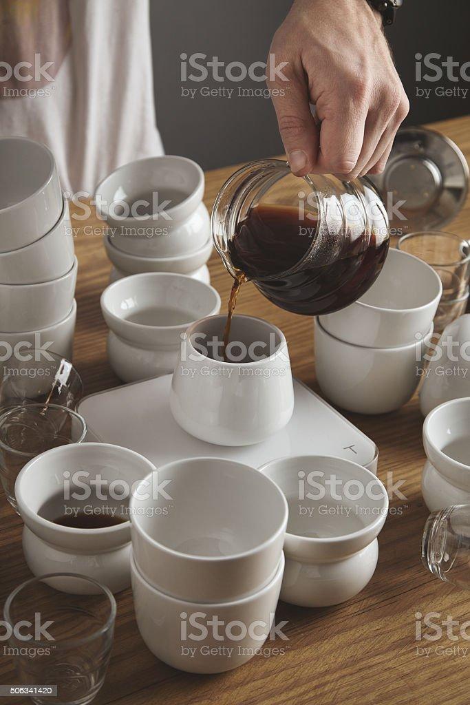 Men's hand holds transparent drip coffee maker pot stock photo