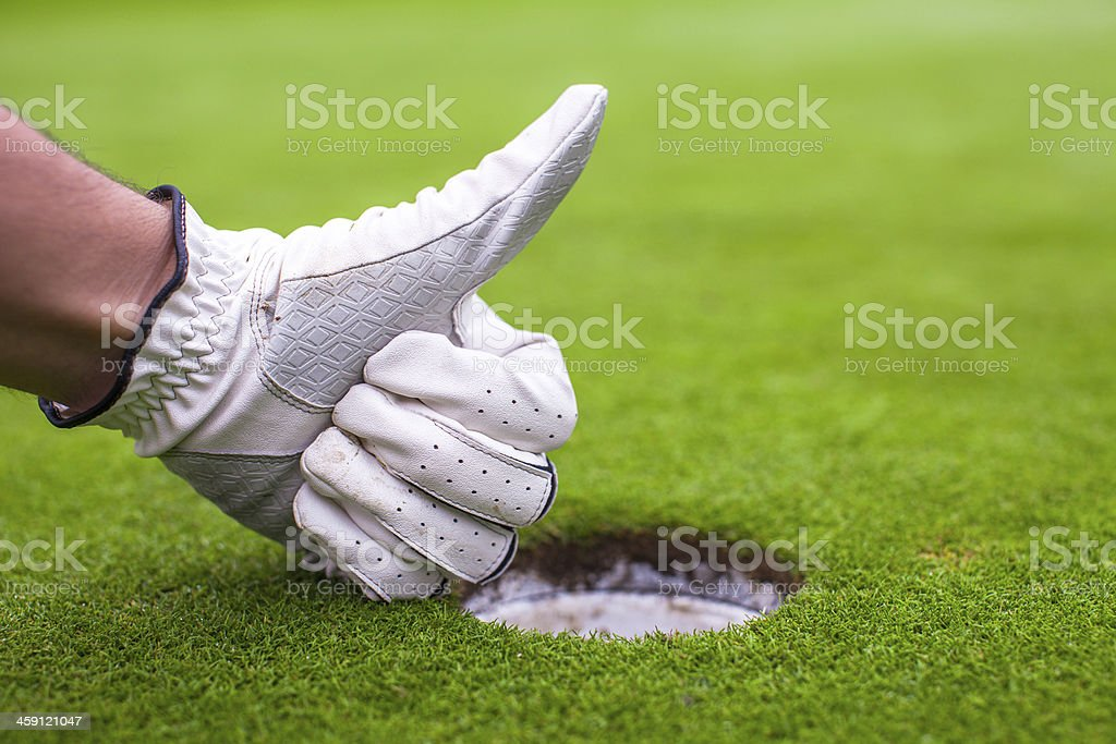 Men's hand in glove golf shows OK near the hole stock photo