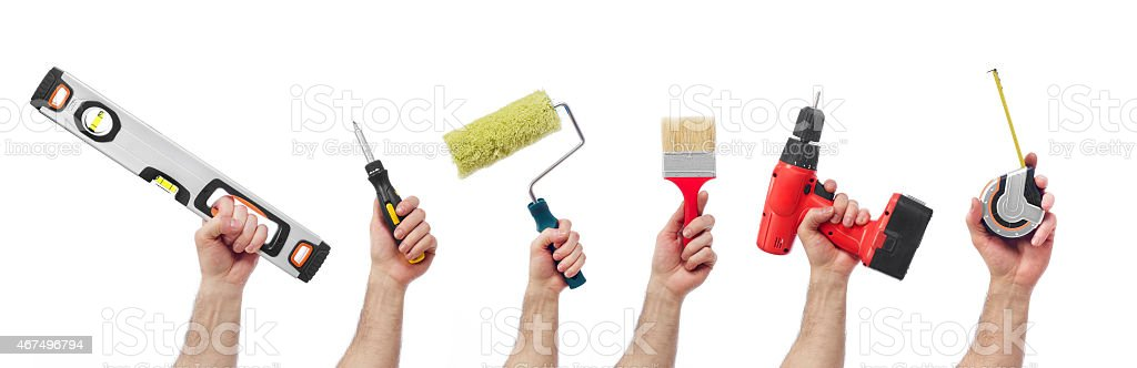 Men's hands holding various decorating tools stock photo