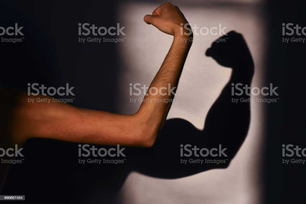 Men's muscles, reality and expectation. Sports and training in the gym. Man's hand and a shadow on the wall. Expectation vs reality stock photo