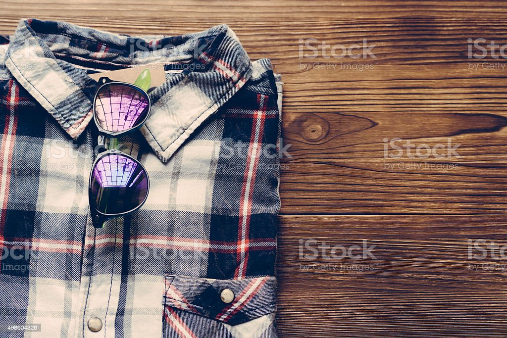 Men's plaid shirt and colored glasses on a wooden background stock photo