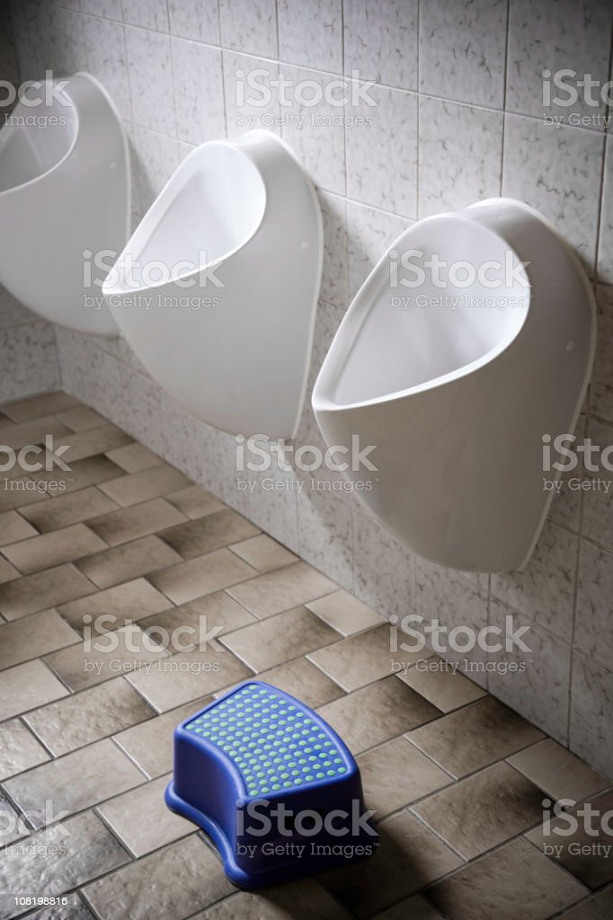 Men's Public Restroom Urinals with Bathroom Pedestal Stool royalty-free stock photo