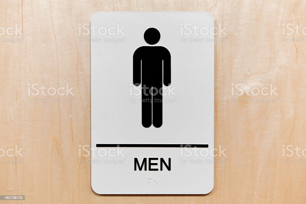 Men's restroom sign with black silhouette on light wood door royalty-free stock photo