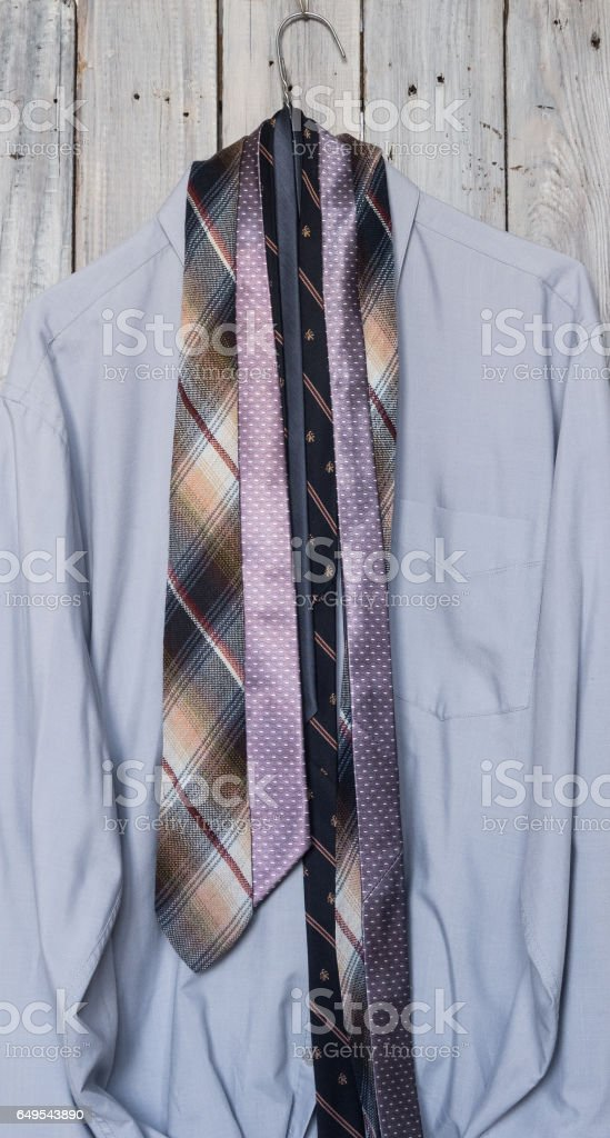 A men's shirt with a five ties hanging on a hanger on a backgrou stock photo