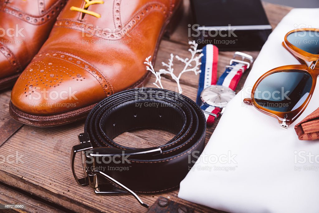 Men's shoes, belt, watch and sunglasses on wooden bench stock photo