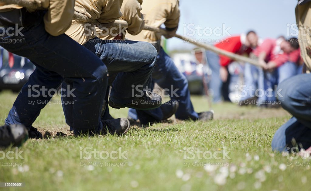 Men's tug of war contest in sunny field stock photo