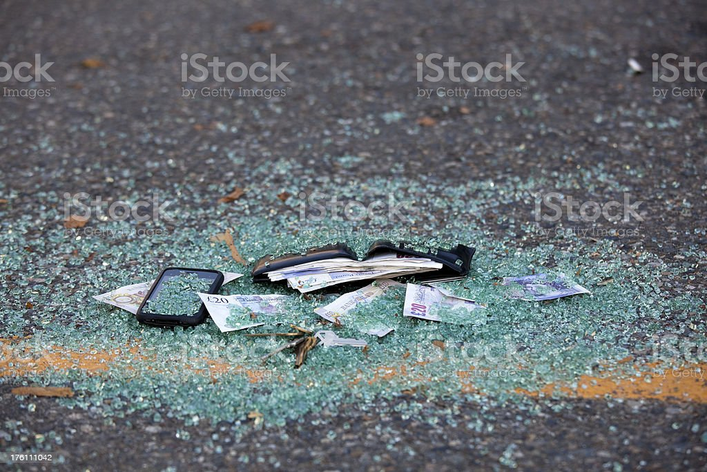 Mens wallet with British Pound Notes, broken glass; crime scene royalty-free stock photo