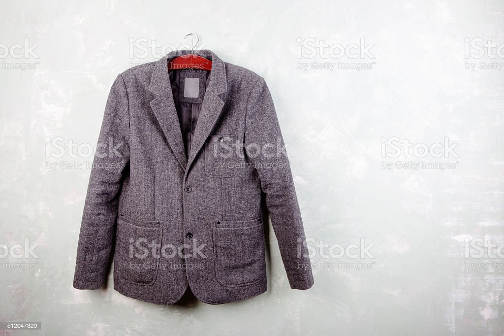 Men's wool jacket hanging on a hanger on the wall stock photo