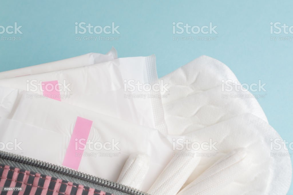 Menstrual tampons and pads in cosmetic bag. Menstruation time. Hygiene and protection stock photo