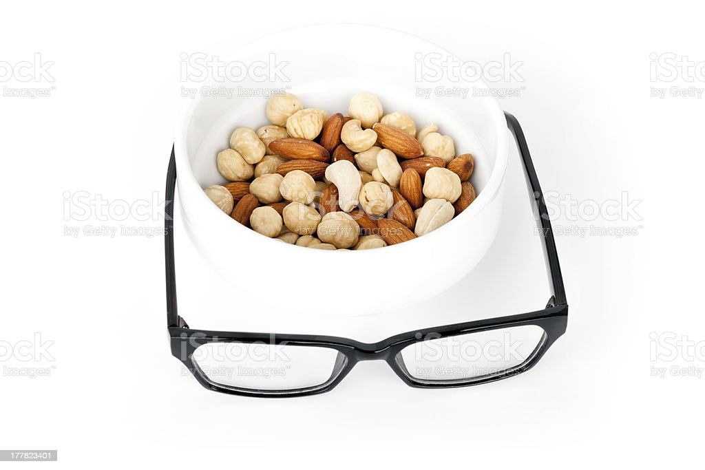 Mental pabulum concept. Nuts in white pot with black glasses royalty-free stock photo