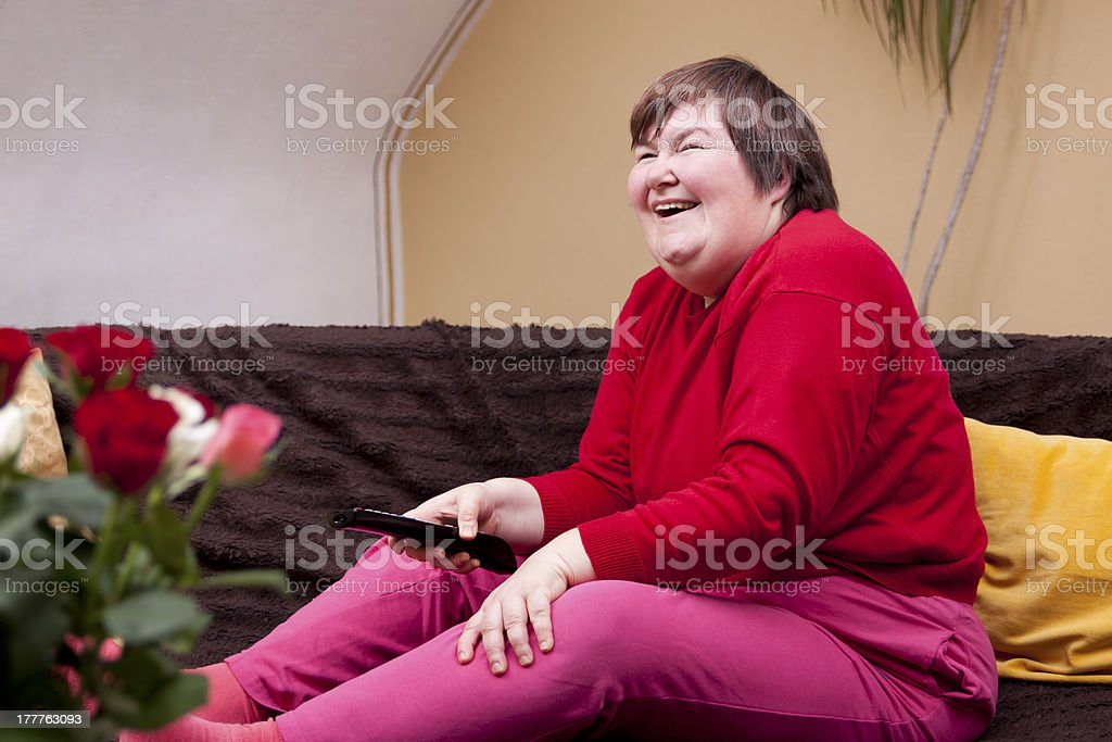 Mentally disabled woman watching television and enjoys stock photo