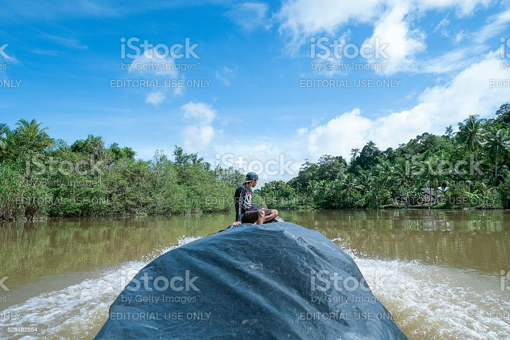 Mentawai tribe crossing the river by traditional canoe. stock photo