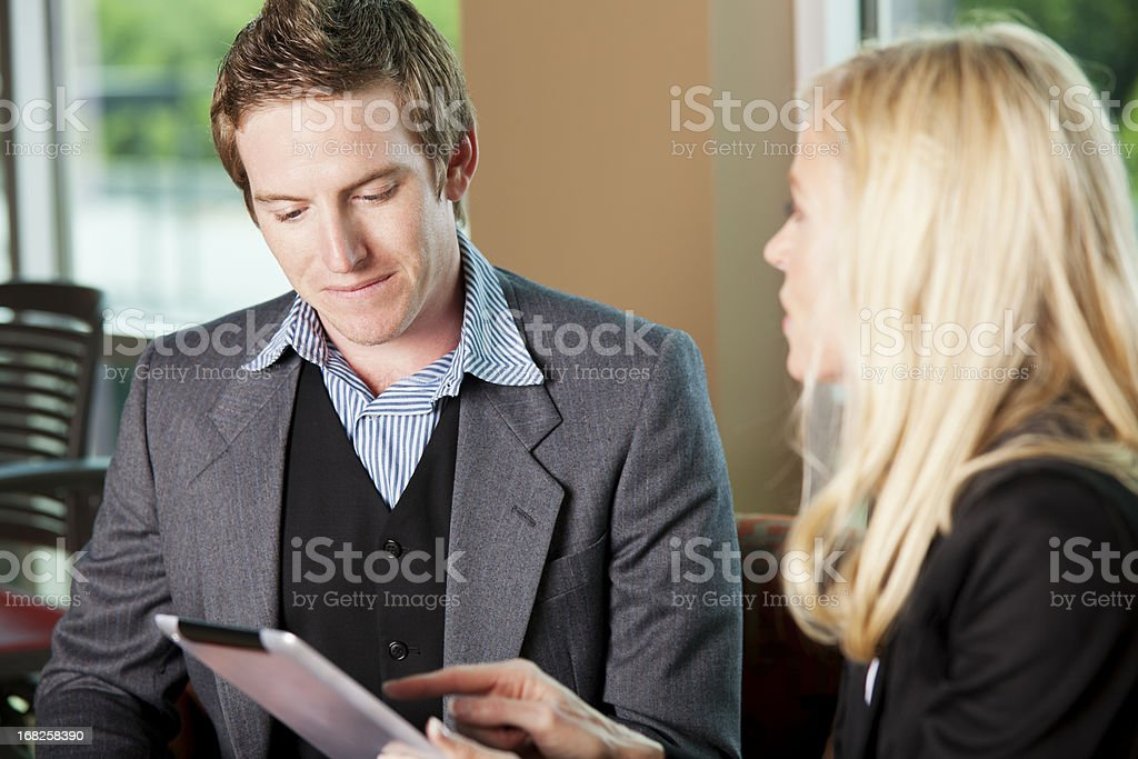 Mentoring: mature woman explaining something to young co-worker stock photo