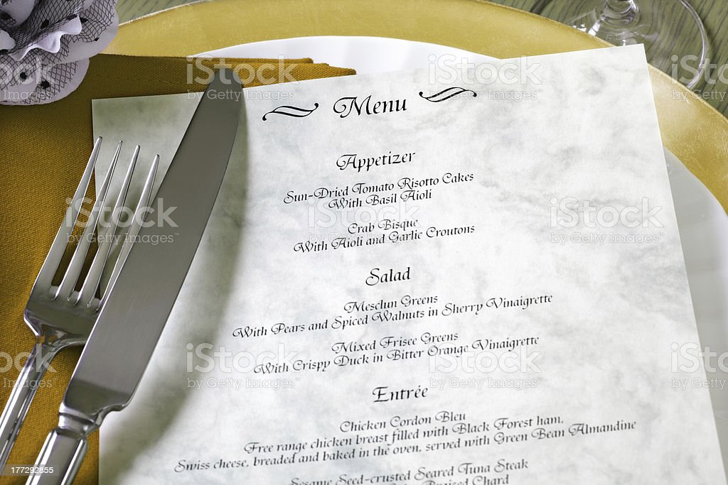 Menu and cutlery on restaurant table stock photo