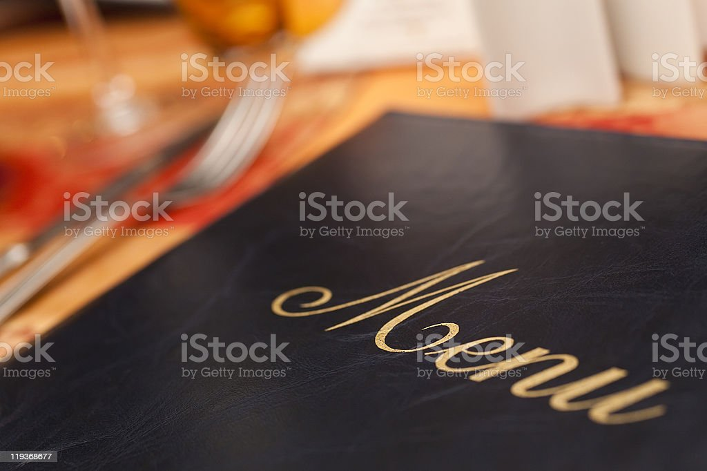 Menu on a restaurant table next to knife and fork stock photo