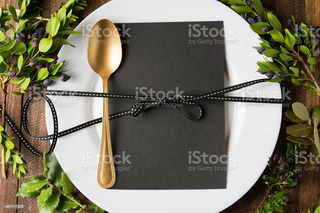 menu place setting with empty card and golden spoon stock photo