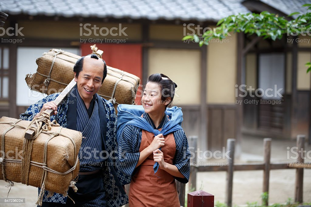 Merchant father and son walking together in old Edo village stock photo