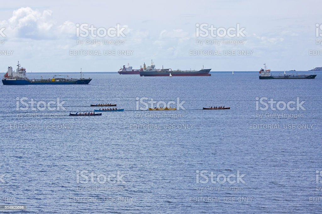 Merchant shipping and gig racing in Falmouth harbour UK stock photo