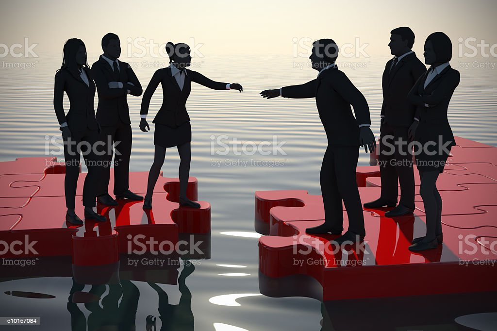 Merger of two teams on a jigsaw puzzle at sunset. stock photo