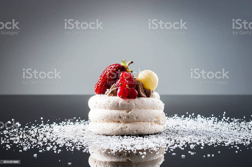 Meringue cake with fruits on a table stock photo