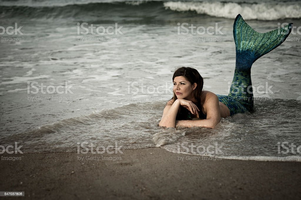 Mermaid resting in shallow waters stock photo