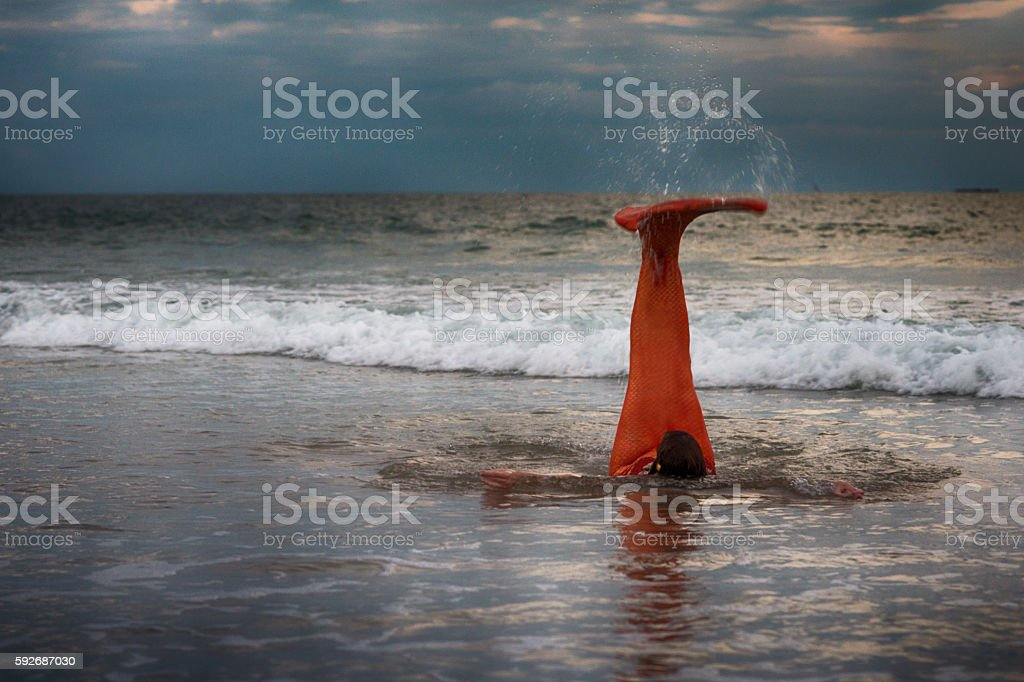 Mermaid with tail straight out of water stock photo